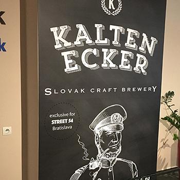 Reklamná tabuľa s oblepenými hranami ukotvená na stene.