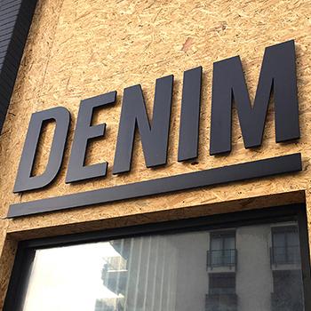 Exteriérové 3D logo nad vstupom do budovy.